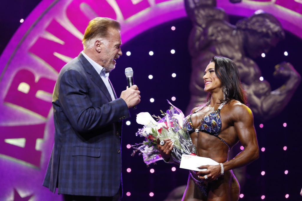2019 Women's Physique  International winner Natalia Abraham Coelho being congratulated by Arnold Schwarzenegger photo by Dave Emery.JPG
